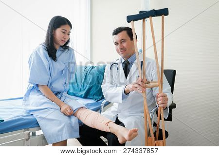 Smiling Doctor And Medical Assistant Takecare To Disabled Patient On Wheelchair