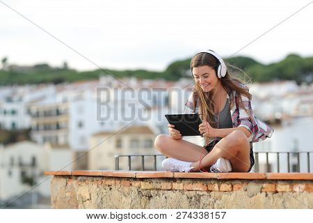 Happy Teen Wearing Headphones Watching And Listening Online Video On A Tablet Sitting On A Ledge On