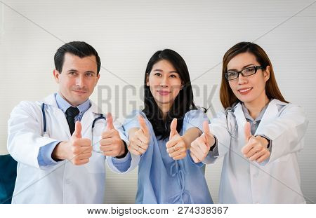 Team Of Doctor And Patient Smiling Giving Thump Up In Hospital.