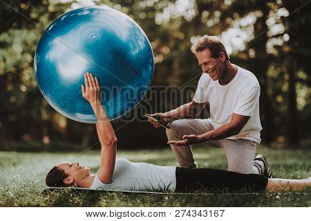 Young Couple In Sportswear Doing Yoga In Park. Sport And Healthcare Concept. Young Man Outdoor. Summ