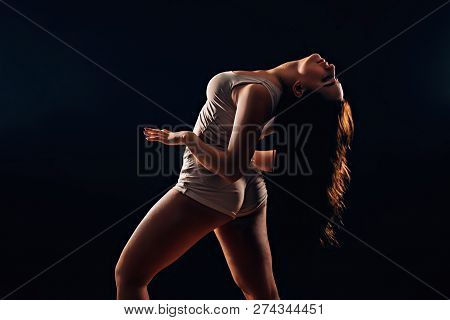 Sexy Brunette Woman With Long Hair Dancing On Black Background In Darkness