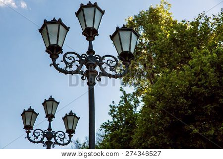 Lamppost With A Triple Lantern With Patterns And Glass Insert In The Park View From Below Against Th
