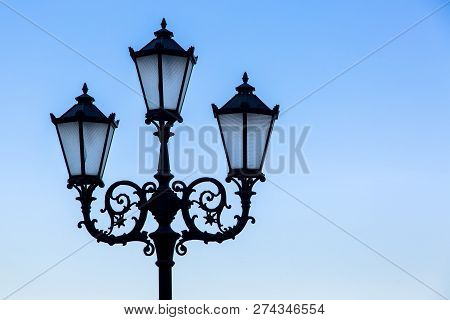 Silhouette Of A Black Street Lamp Against A Blue Sky, Lamppost With Three Wrought Iron Lamps With Gl