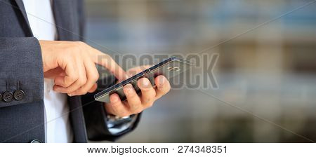 Man Holding Phone. Young Businessman In Business Wear Using A Mobile, Closeup View On Smartphone, Ba
