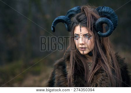 Outdoor Portrait Of Beautiful Young Woman Warrior With Blue Eyes And Specific Makeup Wearing Ram Hor
