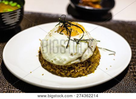 Korean Cuisine - Kimchi Bokkeum Bap (fried Rice With Kimchi, Beef And Fried Egg) On White Plate On B