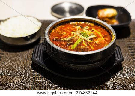korean cuisine - yukgaejang (hot and spicy soup with beef, eggs, mushrooms, starch noodles, scallions, ferns, bean sprouts, served with boiled rice) in metal bowl in local restaurant poster