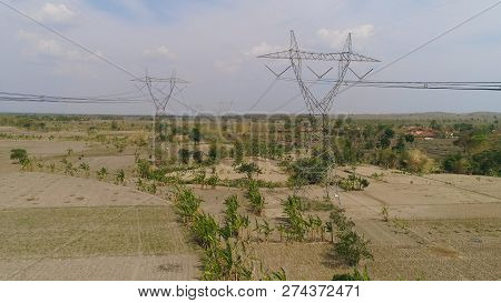 Electricity Pylons Bearing Power Supply Across Rural Landscape. Aerial View Power Pylons And High Vo
