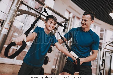 Young Father And Son Doing Exercises In Sport Club. Healthy Lifestyle Concept. Sport And Training Co
