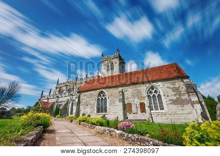 Wooton Wawen Church With Moving Clouds In A Blue Sky