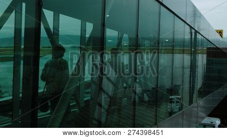 Silhouettes Of Passengers Pass Along The Corridor On A Telescopic Gangway
