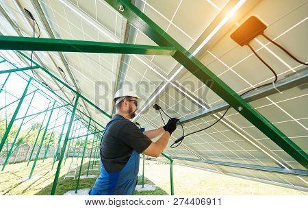 Male Worker Installing Solar Panels During Sunny Day. Perfect Solution For Saving Energy Of Sun, Env