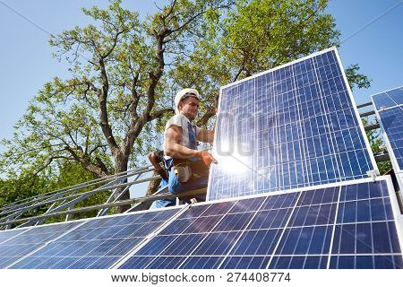 Young Technician Sitting On Metal Platform Adjusting Heavy Solar Photo Voltaic Panel On Blue Sky And