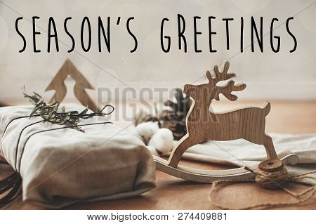 Season's Greetings Text Sign On Stylish Christmas Rustic Gift Wrapped In Linen Fabric With Green Bra