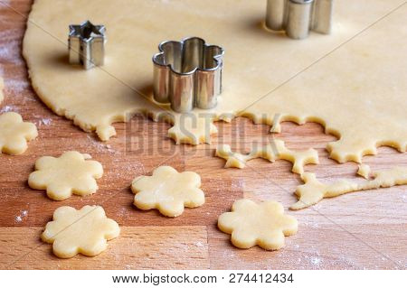Cutting Out Flower Shapes From Rolled Out Dough To Prepare Traditional Linzer Christmas Cookies