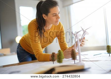 Stunning wind turbine engineer with cellphone planning wind farm placement