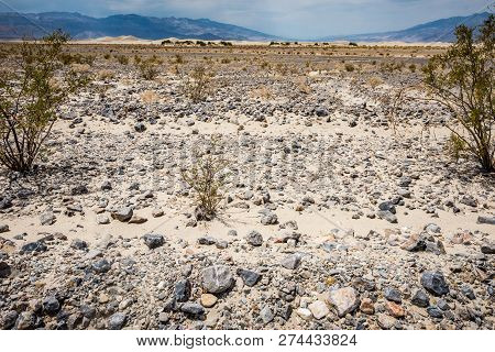 Rocks, Sand And Sagebrush With The Panamint Mountains In Background Of Death Valley National Park