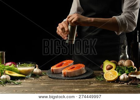 The Chef Prepares Fresh Salmon Fish, Smorgu Trout, Sprinkling Black Pepper With The Ingredients. Fro