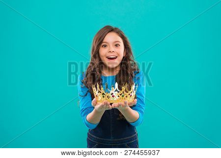 My biggest treasure. Kid hold golden crown symbol of princess. Childhood concept. Every girl dreaming to become princess. Lady little princess. Girl cute baby hold crown while stand blue background. poster