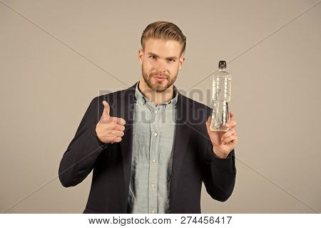 Bearded man show thumbs up to bottle of water. Thirsty businessman with beard in blue shirt and coat. Thirst and dehydration concept. Drinking water for health. poster