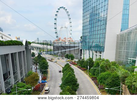 Cars On A Road In Singapore. Singapore Flyer In The Background