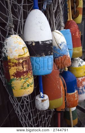 Multicolored Buoys Hanging On Top Of A Net.