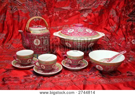 A display of Chinese Porcelain on a red silk chinese landscape painting. poster