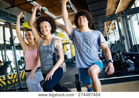 Group Of Young People Doing Exercises In Fitness Club
