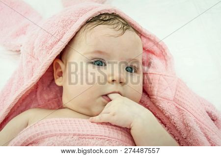 Sweet Caucasian Newborn 3 Months Old Baby Girl Wrapped In A Pink Bath Towel With A Finger In Her Mou