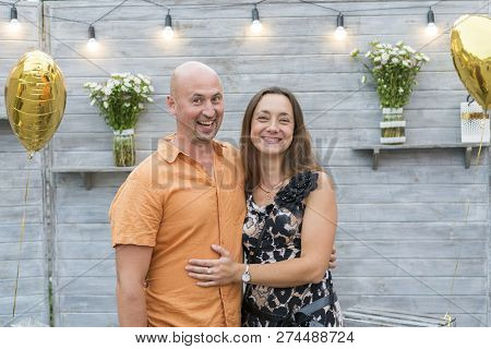 Funny Mature Couple Standing On Grey Background. Middle-aged Couple Standing On Grey Background. Cou