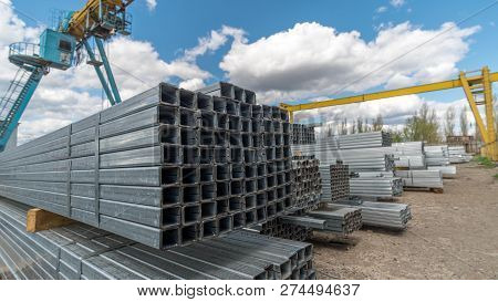 Metallic, Steel Or Aluminum Rectangular Pipes And Tubes On Warehouse. Time Lapse. Moving Clouds