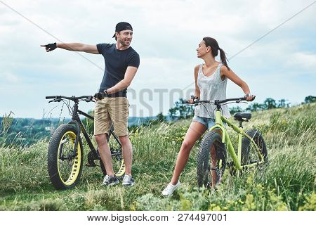 Look At It. A Man And A Woman Are Laughing And Walking Near Their Fatbikes