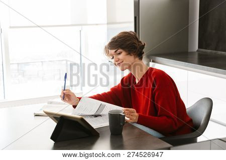 Smiling pretty young woman studying with a tablet computer at the table on a kitchen at home