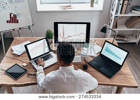 Analyzing Sales. Top Rear View Of Young Businessman In Formalwear Analyzing Data Using Computer Whil
