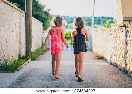 Identical Twin Girls Sisters Walking The Island Streets Of Croatia.