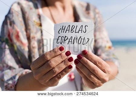 closeup of a caucasian woman outdoors showing a piece of paper with the question hablas espanol, do you speak spanish written in spanish