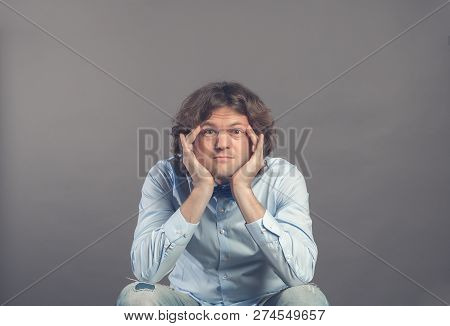 Portrait Of Young Man In Studio, Resting Chin On Hands, While Sitting And Rested Elbows On Knees. Ey