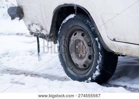 The Road Is Covered With White Snow. Slippy Road. Close Up Of A Cars Tires On A Snowy Road