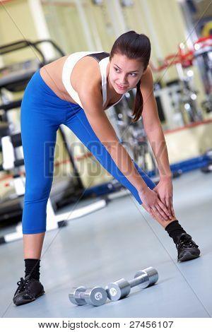 Foto des sportlichen Brünette in Sportbekleidung auf dem Boden stehen und Ausübung im Fitness-Studio