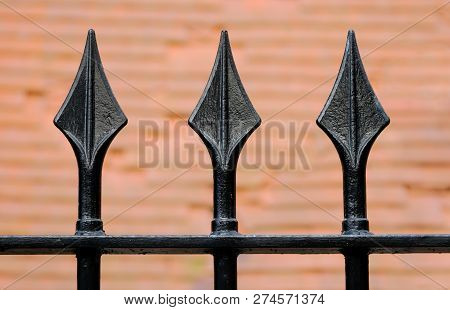 A Black Iron Fence With Three Spikes