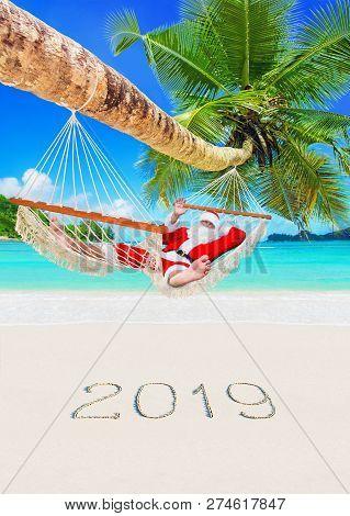 Christmas Santa Claus Relax In Hammock Under Palm At Tropical Sandy Beach, Season Of Happy New Year