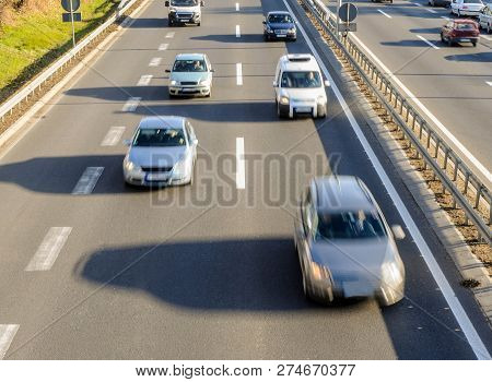 Aerial View Of Cars Driving Fast On The Highway With Three Lanes And Road Fence Barrier