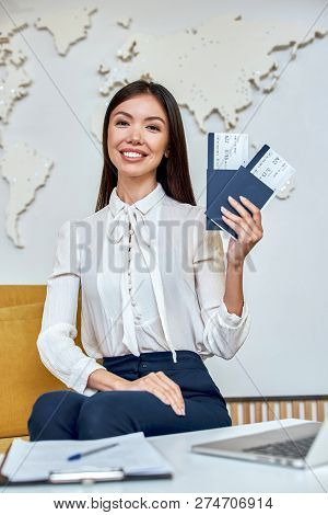 Young Woman Travel Agent With Flight Tickets In Hands