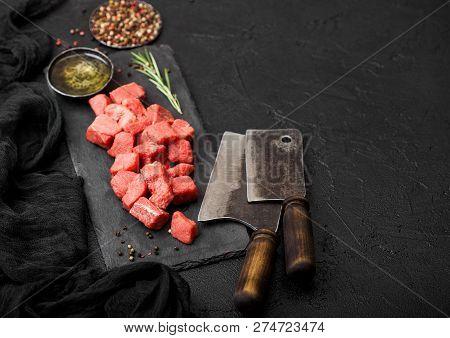 Raw Lean Diced Casserole Beef Pork Steak On Chopping Board With Vintage Meat Hatchets On Stone Backg