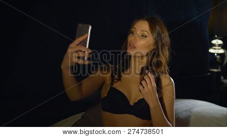 The Girl In Black Underwear Relieves Herself On The Phone. Young Woman Using Technology, Indoors. As