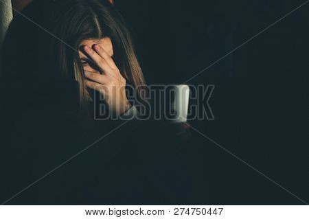 Single Sad Teen Holding A Mobile Phone Lamenting Sitting On The Bed In Her Bedroom With A Dark Light
