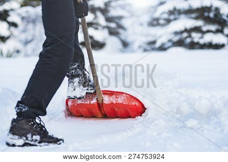 Public Service Worker Or Citizen Shoveling Snow During Heavy Winter Weather