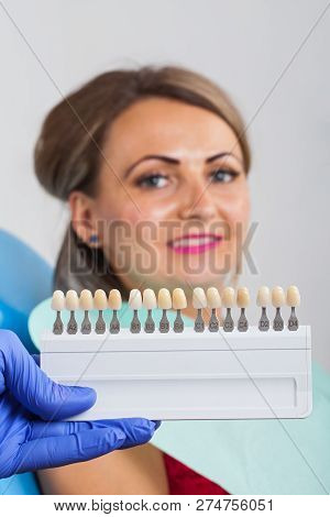 Dental Shade Determination With Shade Guide. Female Patient Wearing Pink Lipstick Close Up