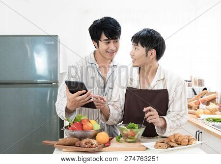 Sweet Gay Couple Looking Recipe In Tablet To Prepare Food In The Kitchen