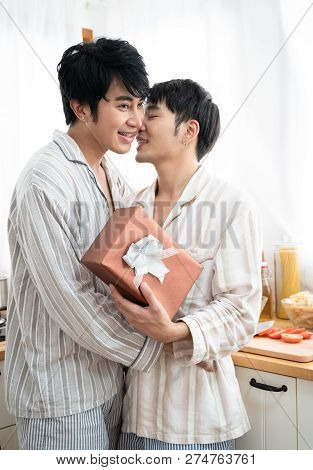 Gay Couple Giving Gift Box To His Boyfriend In The Morning